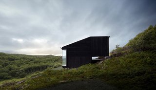 A Matte Black Cabin Steps Down the Steep Slopes of Norway's Stokkøya Island