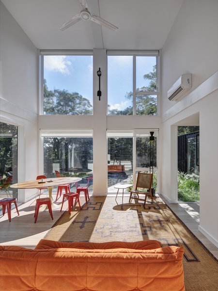 "Taking advantage of the double-height space, the architects created a wall of windows to flood the living area with natural light and frame west-facing views. ""At sunset, rays of light literally go all the way through the house,"" note the architects."