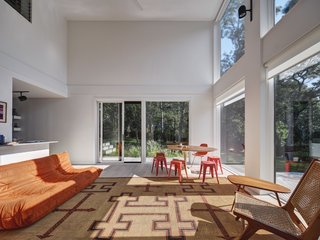 The sun-soaked living area is furnished with a vintage reed mat made by the Tuareg tribe of North Africa (purchased at a flea market), a Toga sofa from Ligne Roset, and a Saarinen table with Tolix red stools.