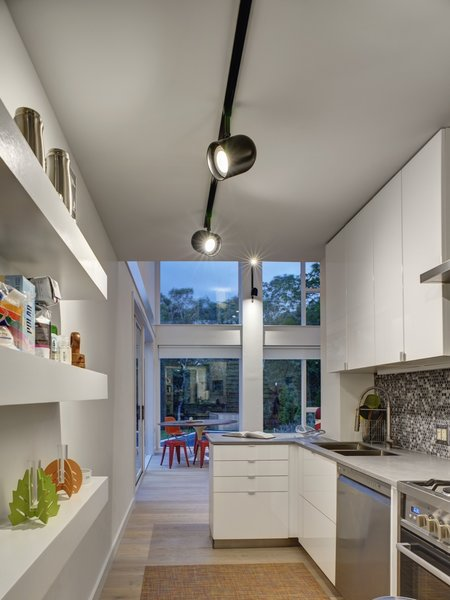 The minimalist kitchen is outfitted with Corian countertops. The floors throughout are bleached oak.