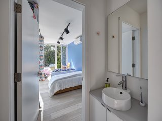 The separated bedroom wing includes one shared bathroom. Large windows and glazed doors fitted into either end of the container create an indoor/outdoor living environment.