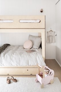 To continue home's minimalist, Scandinavian-inspired theme, the couple purchased Plyroom bunks for their kids. The bedding is from Society of Wanderers.
