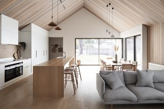 """The raked red cedar ceiling is one of the couple's favorite aspects of the home. They are particularly enamored with """"the small shadow lines we created in the junction between the raked ceiling and the plaster bulk heads…it's such a tiny detail that tightens everything up."""""""
