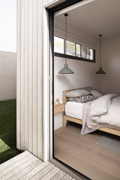 A sliding door connects the master bedroom to the backyard, where an alfresco outdoor entertaining area and outdoor shower are located.