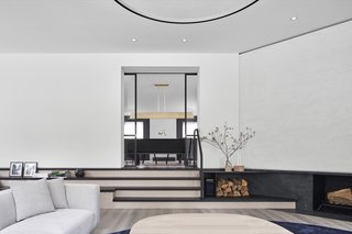 """On the main floor, sliding doors with large glass panes framed in black steel pair modern minimalism with traditional panel-door proportions,"" say the architects."