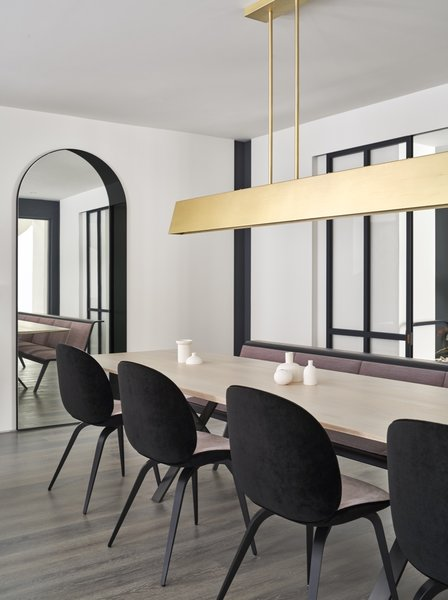 The dining room occupies the threshold between the sunken family room (past the sliding glass doors) and the living room. The reconfigured layout and removal of a dividing wall help unify the formerly disparate spaces.