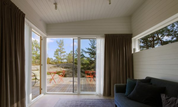 The living room seamlessly connects with the outdoor terrace. Oiled pine is used for both the indoor flooring and outdoor deck.