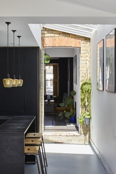 """The brick pictured is original to the home. """"We wanted to connect our new extension against the retained rear wall of our house as a feature and acknowledgement of the original building,"""" says Richard. """"The doorway/opening is actually the original doorway into our side alleyway and garden—we just removed the doors and tidied up slightly."""""""