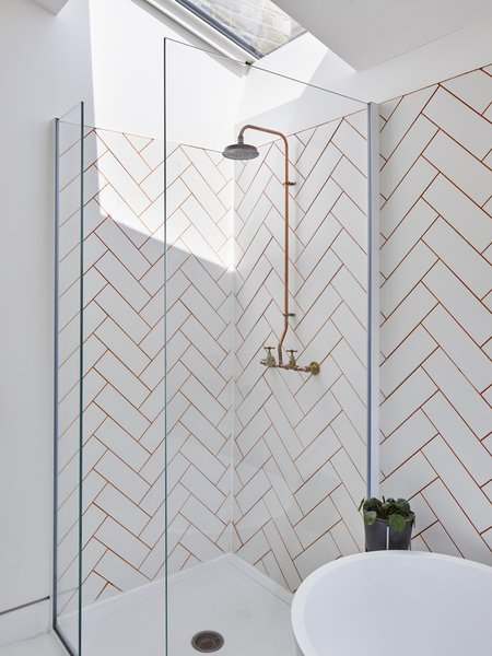 An existing bedroom was sacrificed to make room for a first-floor bathroom, which is fitted with a large skylight. The herringbone wall tiles are from Topps Tiles.