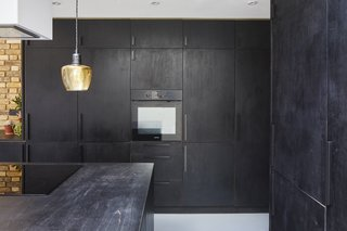 Beautiful yet practical materials define the home—such as the Indian ink–washed plywood used for the kitchen cabinetry. Purchasing secondhand furnishings from eBay also helped keep costs low and add personality to the home.