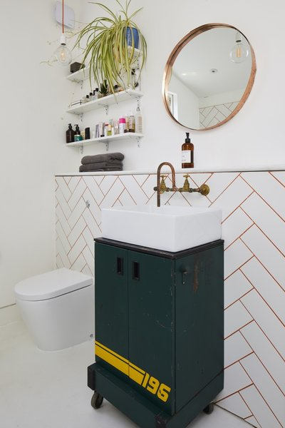 The crafty couple made all of the bathroom's copper fixtures, as well as the mirror. The 196 wheeled cabinet was an eBay find.