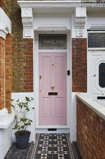 """We couldn't resist this beautiful shade of pink,"" notes Richard of the door color. ""It was championed by Kristina, but I didn't take much convincing. It would also draw a lot of attention and help the house to be easily found by visiting clients and potential new business."""