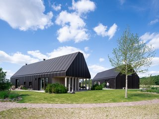 The Dutch 'hoeve' informed Villa Vught's material palette of dark bronze anodized aluminum cladding that wraps both the facade and the roof in a nod to the corrugated iron rooftops of nearby farm buildings.