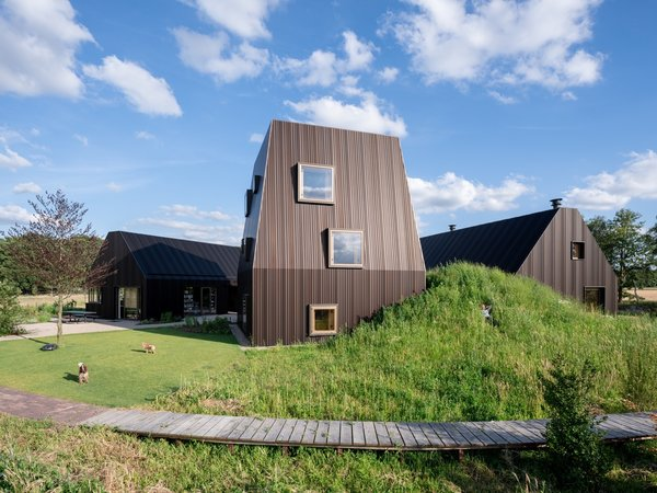 The barn-shaped pair of gabled buildings flank a taller volume for visual contrast. The grass mound conceals a passageway that connects the two buildings on the right.