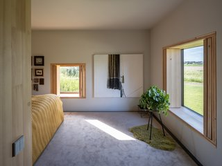 The master bedroom overlooks views of the fields. Folding wooden screens were installed in place of curtains.