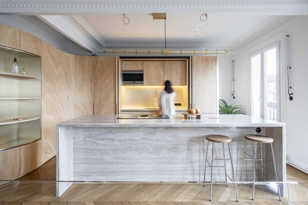 Sculptural plywood walls weave new life into a 19th-century Parisian apartment while preserving its historic Haussmannien features.