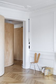 The new wooden partition provides a sculptural counterpoint to the historic apartment's ornate elements and rigid geometry. The original herringbone hardwood floors were refinished throughout.