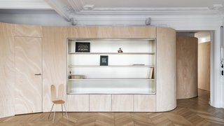 The wooden ribbon features integrated storage. The display shelves are backed by decorative brass panels by Egger.