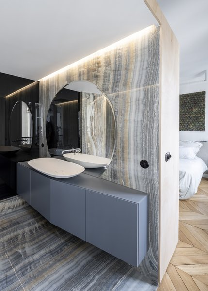 """Massive gray onyx-style porcelain tiles give the master bath a luxurious appearance. """"The tiles for the bathroom and kitchen were so hard to get to the fifth floor with a tiny elevator,"""" notes the architect. """"They were three meters by one-and-a-half meters, and getting them upstairs and cutting them on-site was really complicated."""""""