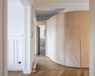 The new wooden walls stop short of the ceilings, preserving the moldings and the outline of the historic floor plan.