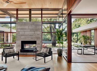 Walls of glass promote constant connection with the outdoors. The chairs that flank the double-sided fireplace are Kenmare armchairs by Modloft.