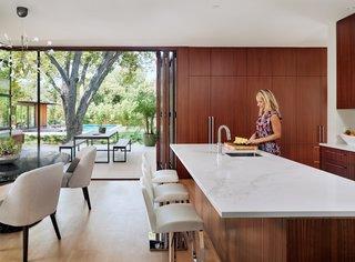 Folding glazed doors open up to seamlessly connect the open-plan kitchen and dining room to the courtyard. The kitchen is dressed with Sapele Mahogany cabinetry, Caesarstone Stratuario Maximus countertops, and rift-sawn white oak flooring.