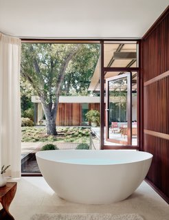 Walls of glass blur the boundary between indoors and out in this bathroom. The floors are Jerusalem Bone limestone.