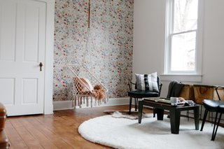 The room was remade into a lounge and game room. The accent wall is covered with Anthropologie Sketched Songbird wallpaper.