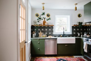 Fitted with new windows, the light-filled kitchen has become the designers' favorite part of the project because of its dark green tones with wood and brass accents. The kitchen renovation budget was approximately $15,000.