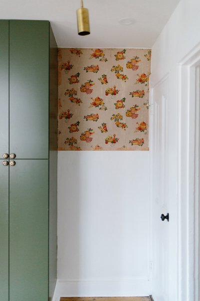 "Note the scrap of 19th-century wallpaper in the kitchen. ""We managed to save it, and I just adore the charm and color it brings,"" says Claudia. ""I am thrilled to the bone when I am able to tell a small piece of the story of the original homeowner's style."""