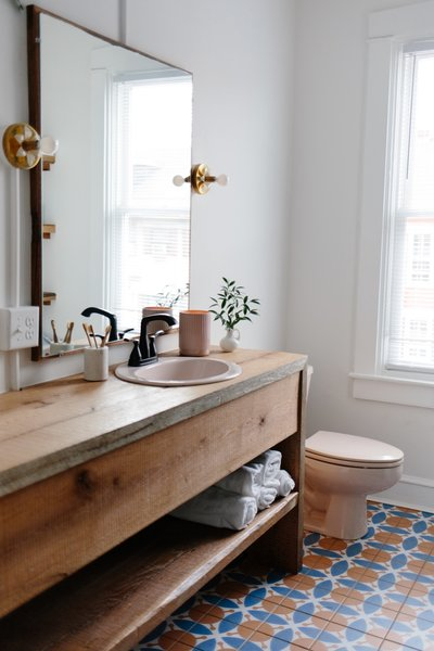 The wood waterfall vanity was built by Chris' brother, Jeremy, who used oak wood reclaimed from an old barn that was then sanded down and finished with water-based polyurethane.