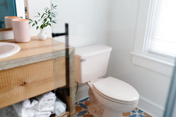 """Since the home had to be completely gutted, few original elements were kept. To bring character and sense of age back to the home, Claudia spent two weeks scouring the internet for a vintage toilet and sink and settled on the """"perfect blush set"""" salvaged from a 1970s home."""