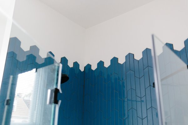 A bold blue/black tiled shower with glass panels brings new life to the bathroom.
