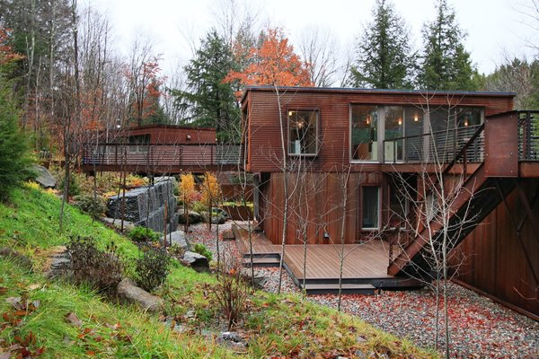 To minimize energy use, the residence relies on natural ventilation for cooling. Heat is provided by an inflow hydronic tubing system. Note the guesthouse seen behind the bridge.