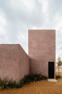 """""""We wanted to give a natural feeling and some color related to the surrounding earth—but we wanted to have a finish that would age well, so we avoided the use of paint on the outside,"""" explain the architects regarding the home's pink concrete plaster."""
