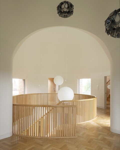 The sweeping, curved oak staircase with an oak balustrade leads to the first floor, which—unlike the ground floor's polished concrete flooring—features herringbone oak parquet floors. Underfloor heating is powered by a 12kW ground-source heat pump with 600 meters of pipe buried in the garden.