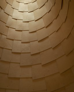 To mimic the exterior, the architects covered the interior of the roof cones with overlapping plywood shingles to create a continuous surface.