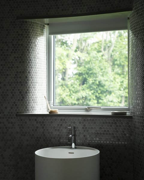 """A peek inside the downstairs bathroom, which is covered in mosaic tiles that echo the microcement finish used throughout the home. """"As it is a north-facing room, matte and gloss finishes have been employed to play with reflections from sunlight as it enters the space,"""" note the architects."""