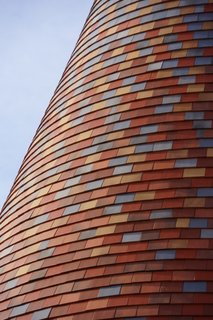 The home's facade is covered with over 41,000 Kent-style tiles that were locally produced with traditional craft skills in six shades—from dark red at the base to light gray at the top.