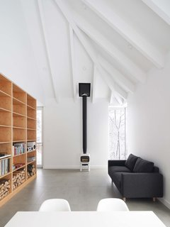 The walls and ceilings are painted white to match the exterior and the snowy landscape. The living room sofa is from Élément de Base, and the wood-burning stove is a Jøtul F 105.