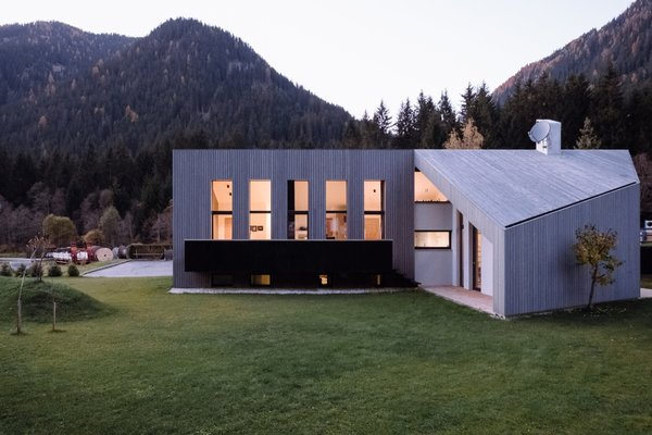 """When viewed from the rear, the home's sculptural shape becomes more apparent. """"At first sight, the requested pitched roof is not recognizable,"""" say the architects. """"Only if seen in direct elevation, from above or experienced from inside in section it is visible and gives a spatial tension to the whole."""""""