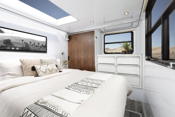 The master bedroom is furnished with a queen bed and a cool-touch 10-inch memory foam mattress beneath a large skylight. Compared to last year's model, the 2020 Living Vehicle offers two feet of extra space.