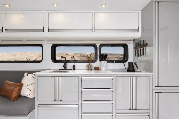 The compact kitchen is equipped with a 12.5-cubic-foot fridge and freezer; a moveable kitchen island with storage; a cooktop with range hood; a water filter; a pull-out trash can; a microwave; a faucet; and a pantry. Other appliances, such as a dishwasher and wine cooler can be added on.