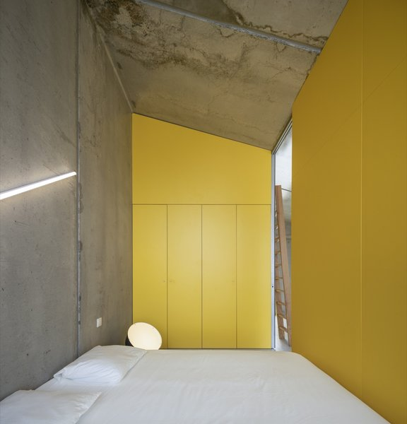 Accessed via full-height sliding doors, this bedroom is filled with light from the unit's fully glazed wall.