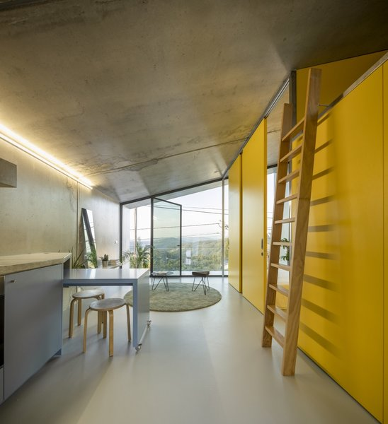 In contrast to the building's gray concrete exterior, the residence interiors feature bright pops of color from pastel blues to vibrant yellows.