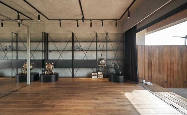 Surrounded by gray Pandomo walls and black (instead of rose gold) steel shelves, the multipurpose room has a more masculine feel compared to the rest of the home. Sliding doors open up to an outdoor terrace.