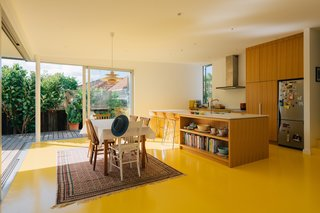 """The high-gloss yellow imparts a warming reflection over the crisp white walls and the occupants,"" says Mulla. ""The result is a home that perpetually feels fun, warm, and friendly."""