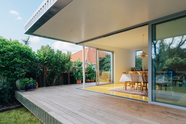 The deep roof overhang provides protection from the sun and bounces reflected yellow light from the floor.