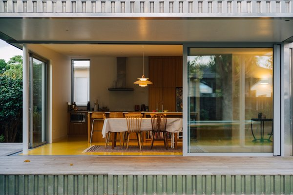 Glazed doors slide open to seamlessly connect the living spaces with the outdoors.