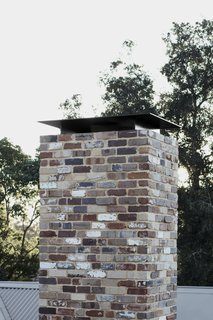 The brick vents, openings, and chimney flue are protected from falling embers.